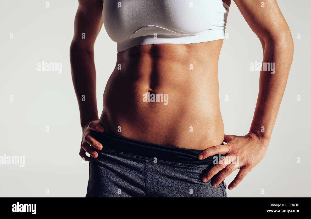 Slim and fit woman belly. Torso of fitness female. Mid section of woman body with muscular abs on grey background. - Stock Image