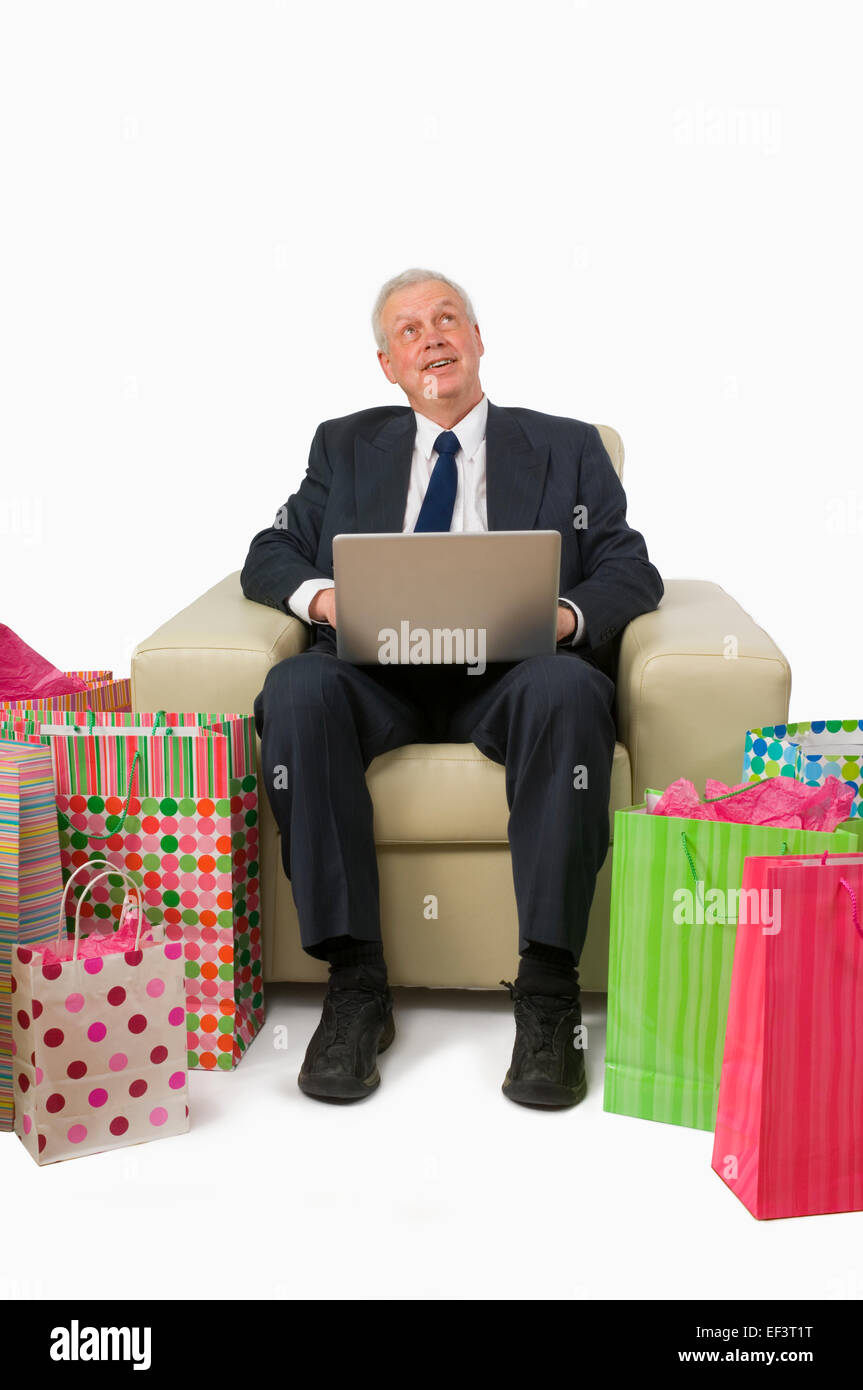 Daydreaming businessman surrounded by gift bags - Stock Image