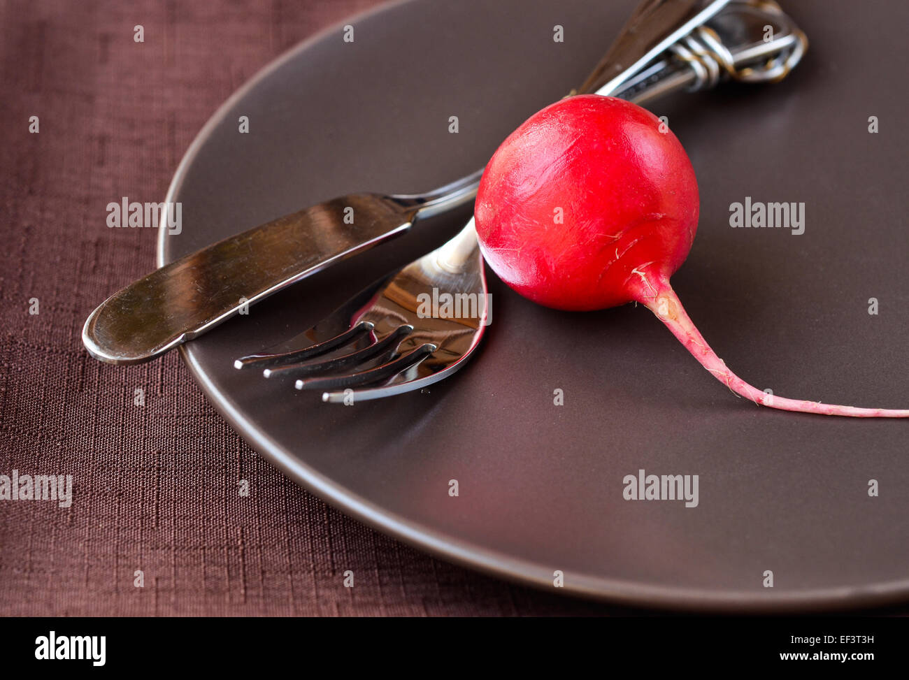 Single radish and silverware on a plate - Stock Image