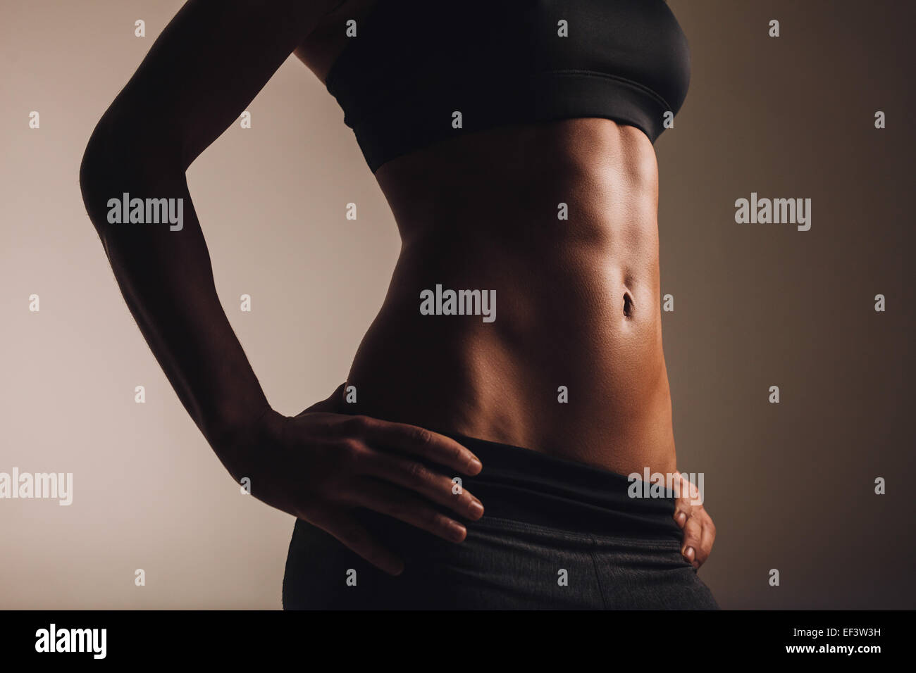 Mid section of strong young woman torso with her hands on hips. Abs of female  athlete in sportswear. - Stock Image