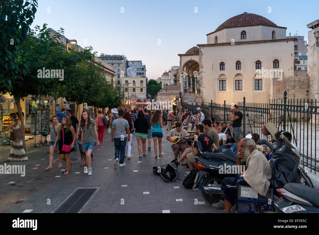 Holiday makers, tourists, market sellers and buskers on Monastiraki, Avissynias Square, Athens, Greece - Stock Image