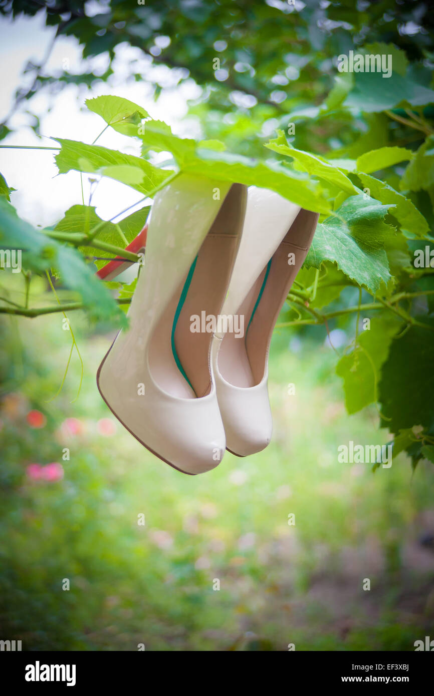 Womens shoes with high heels are hanging - Stock Image
