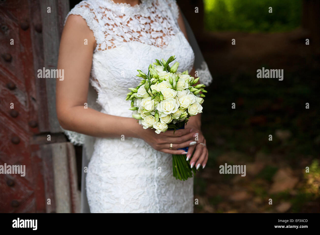 Bride holding wedding flower bouquet of roses. - Stock Image