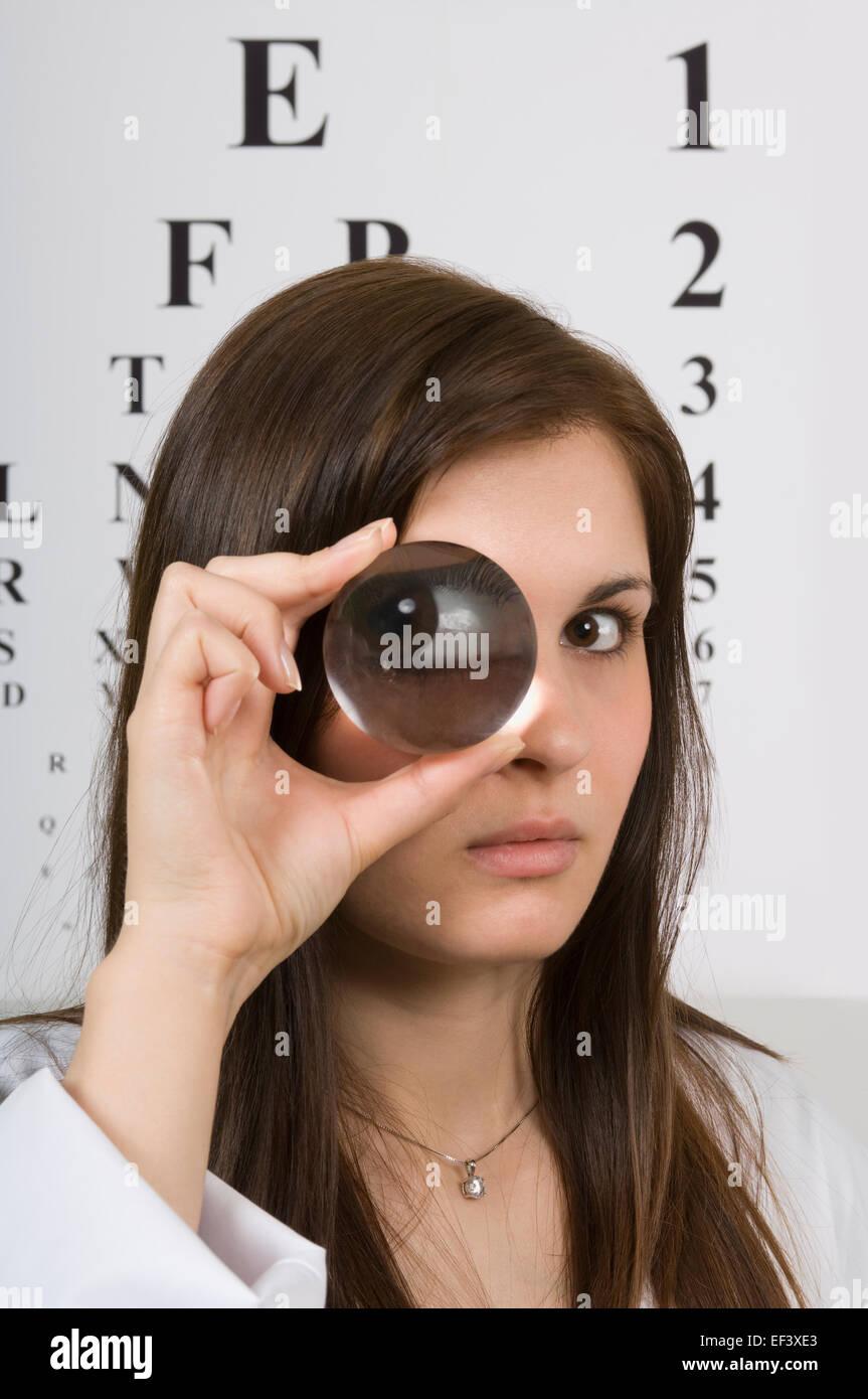 Optometrist looking through lens - Stock Image