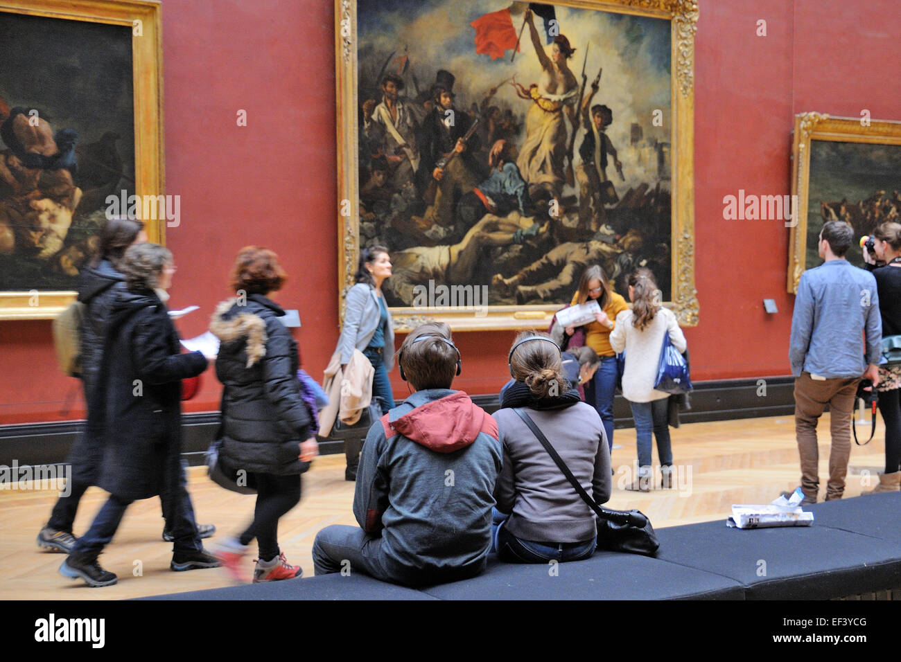 PARIS - MAR 1: Tourists look at the paintings of Eugene Delacroix at the Louvre Museum (Musee du Louvre). - Stock Image