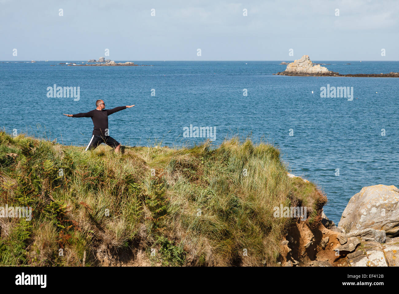 Man doing tai chi on a clifftop near Landéda, Les Abers, Finistère, Brittany, France. - Stock Image
