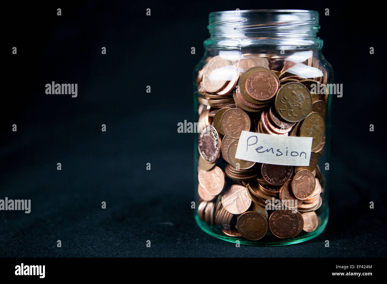 A glass jar holding 1 and 2 pence coins with a label saying 'Pension'. Text space left. - Stock Image