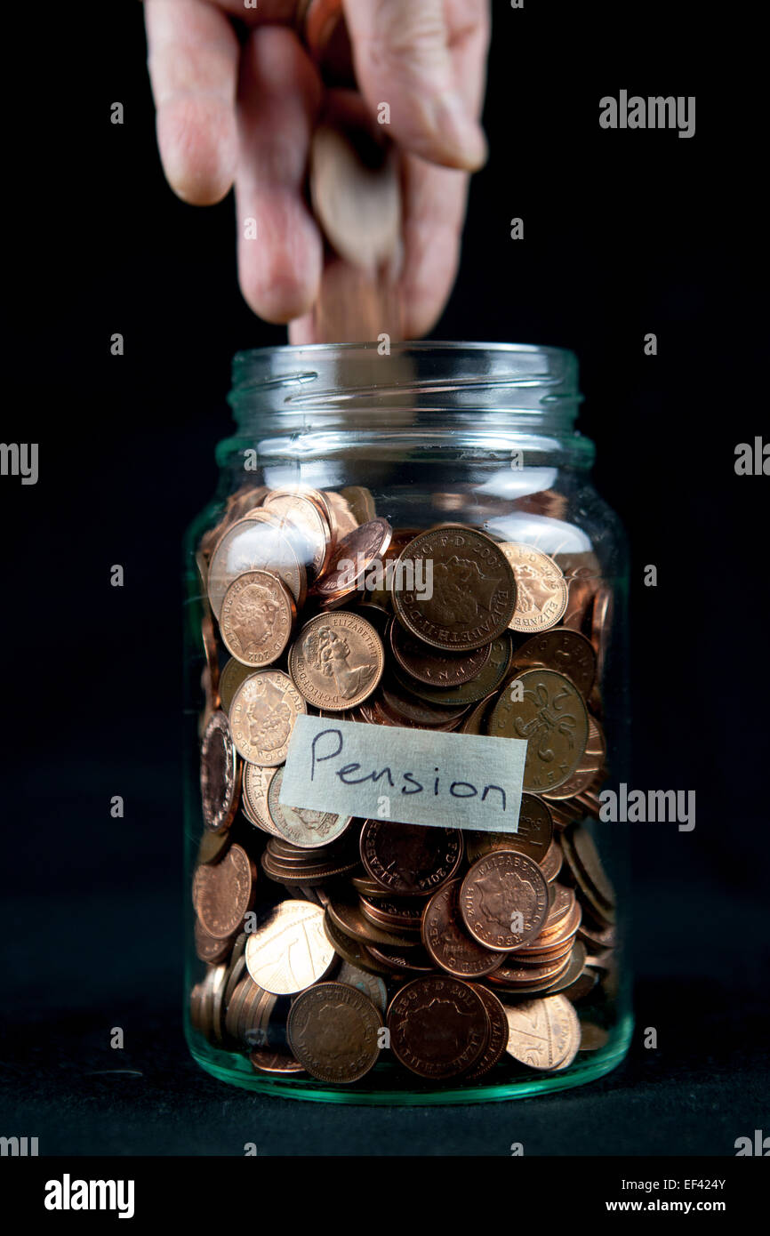 Adding some pennies to a pension pot. - Stock Image