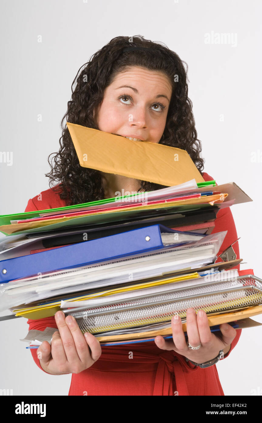 Woman carrying large stack of paperwork - Stock Image