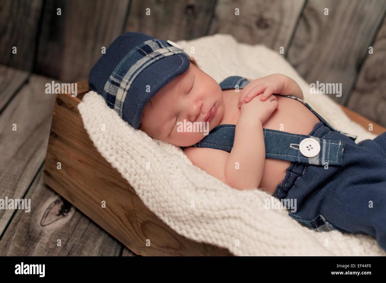 An eight day old newborn baby boy wearing a blue newsboy cap d4f1bcde89bc