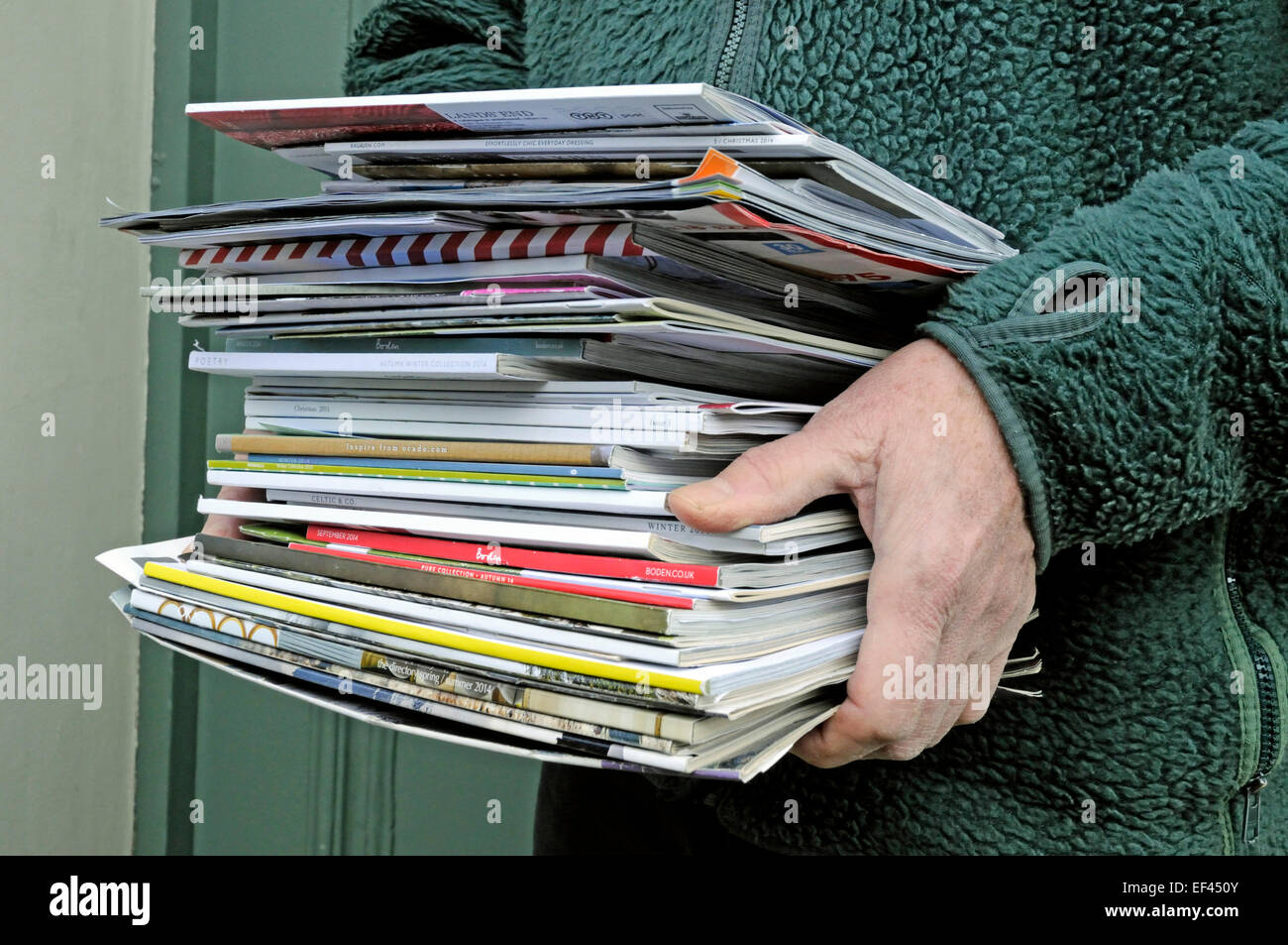 Man's hands holding pile of catalogues for recycling, Holloway, London Borough of Islington, England, UK - Stock Image