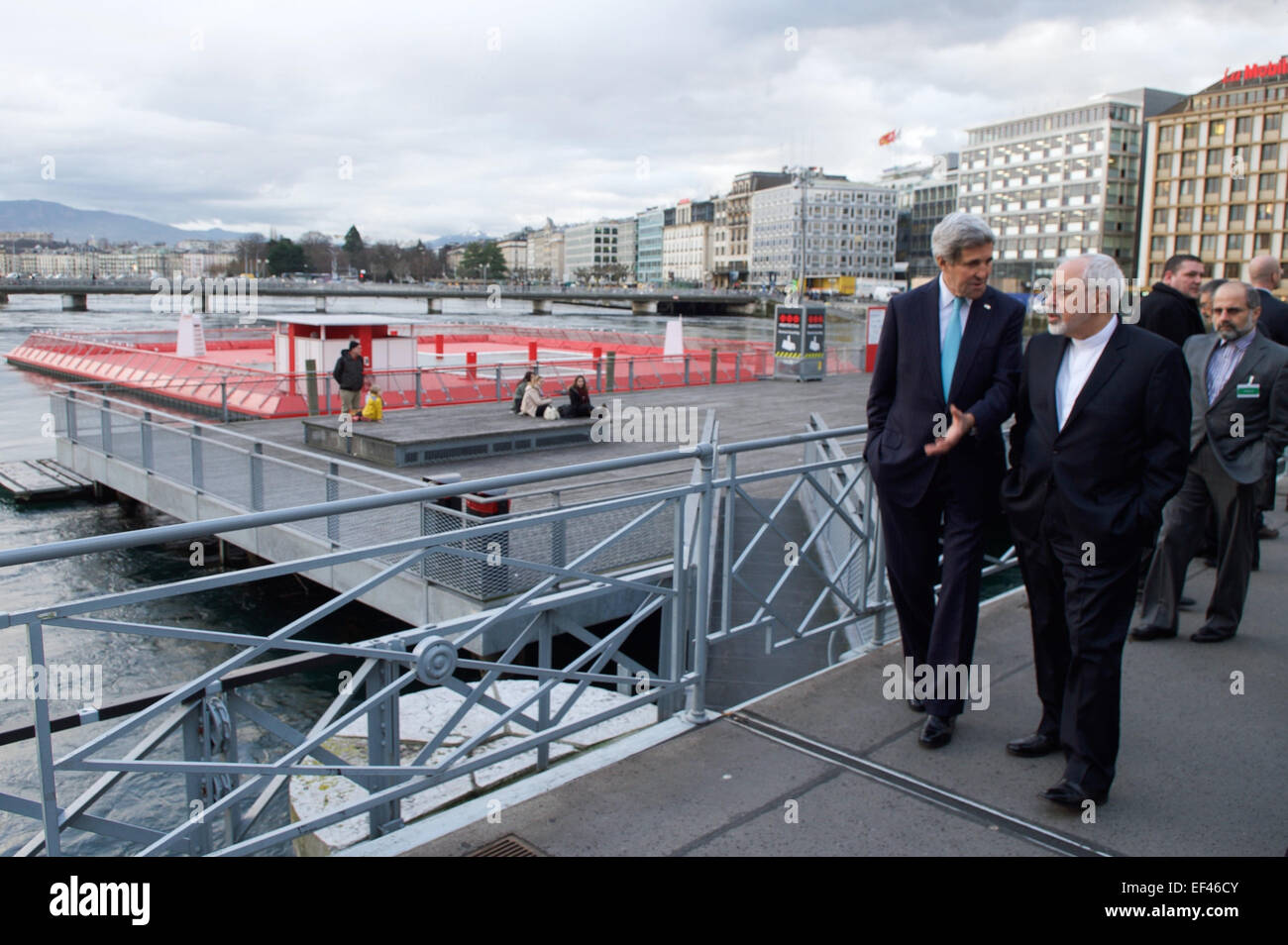 U.S. Secretary of State John Kerry and Iranian Foreign Minister Javad Zarif chat as they cross the Rhone River on - Stock Image