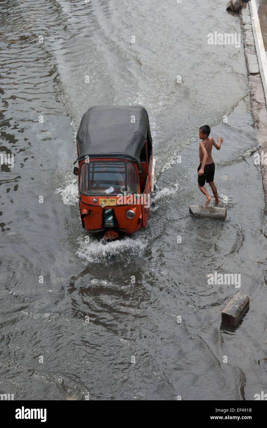 Bajaj auto rickshaw passes through flooded street in Jakarta. Stock Photo