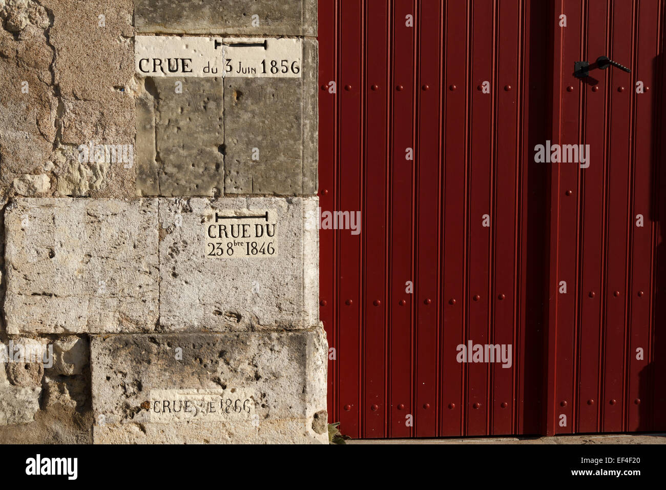 Writing historic flood level on a stone wall beside a red door, Amboise, Indre et Loire, France. - Stock Image