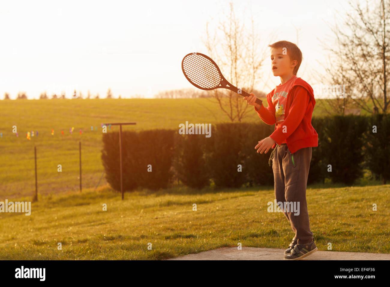 boy playing tennis in backyard - Stock Image
