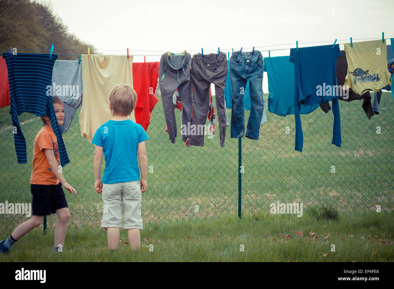 boys playing walking, laundry hanging - Stock Image