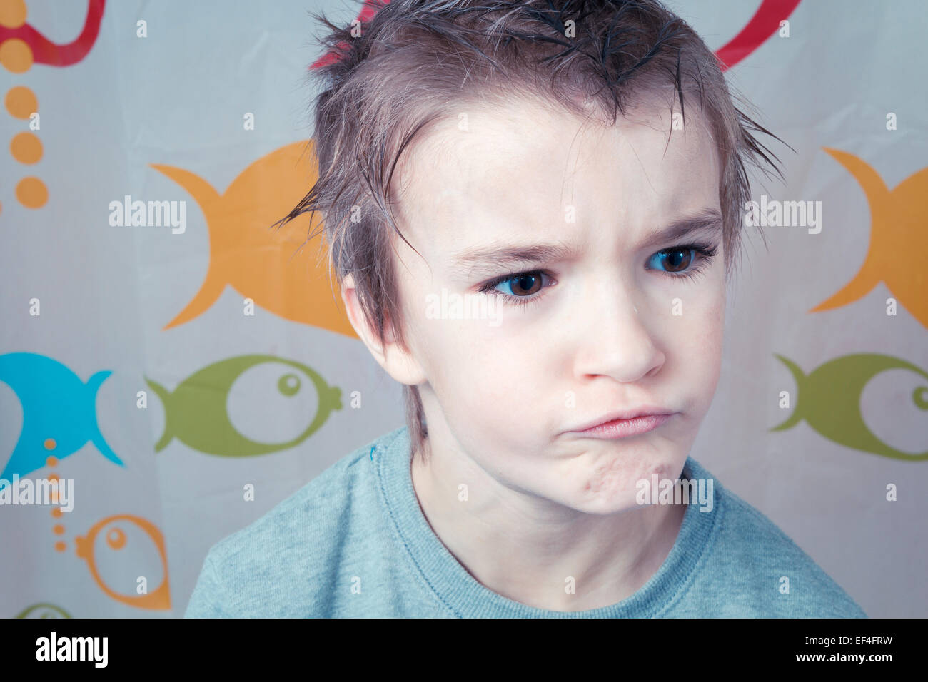 Young boy in bathroom making a face. - Stock Image
