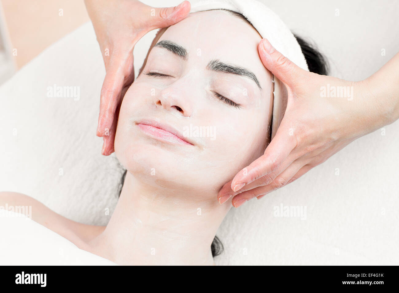 Young woman facial massage in beauty parlour - Stock Image