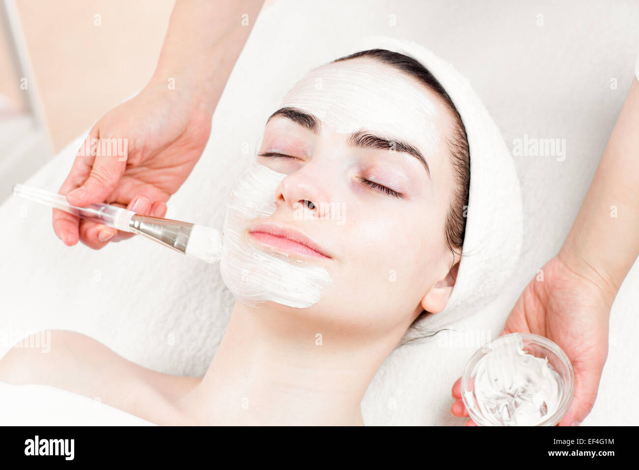 Young woman facial mask applying in beauty parlour Stock Photo