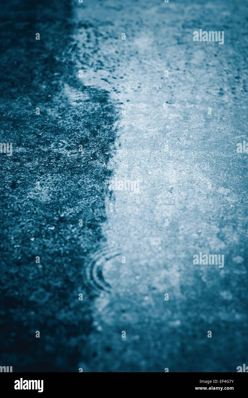 Water droplets hitting wet surface. - Stock Image