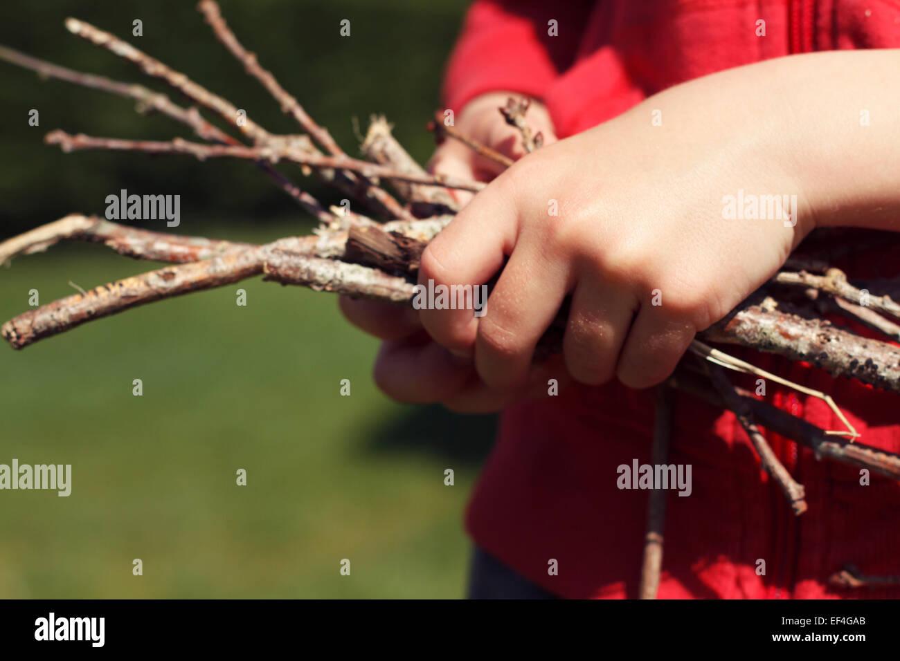 child holding wooden sticks close up - Stock Image