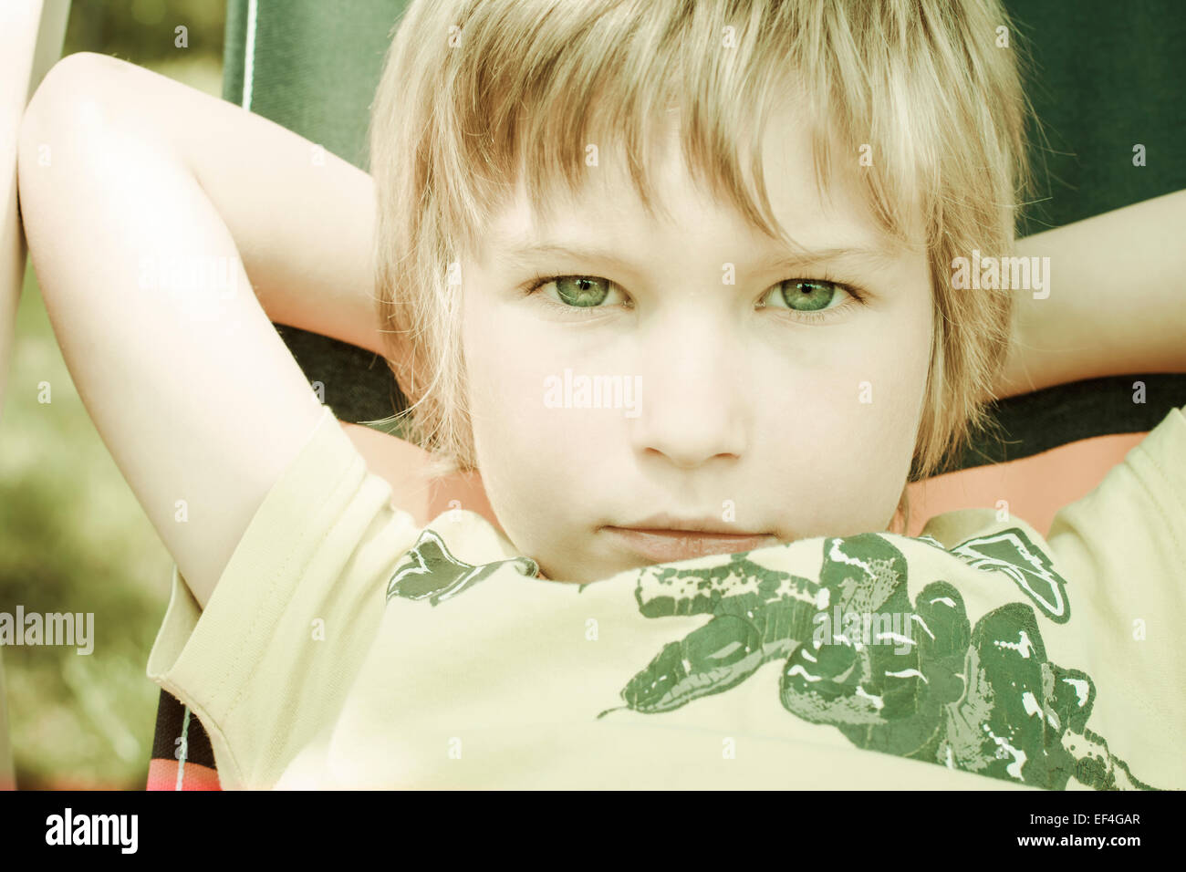 boy sitting deck chair, 6 years - Stock Image