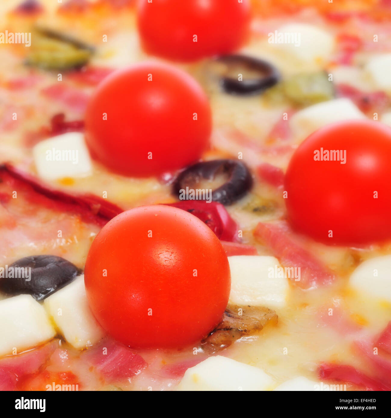 closeup of a pizza with bacon, olives, cherry tomatoes, goat cheese, green pepper and eggplant - Stock Image