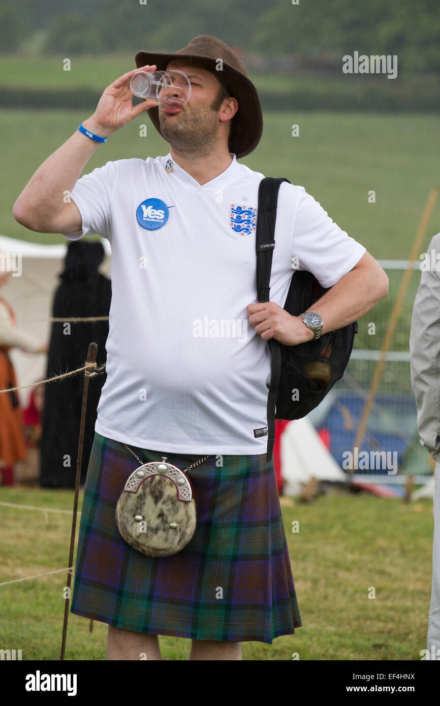 A man in a Scottish kilt, wearing an England football shirt and drinking a beer during events at Bannockburn Live, - Stock Image