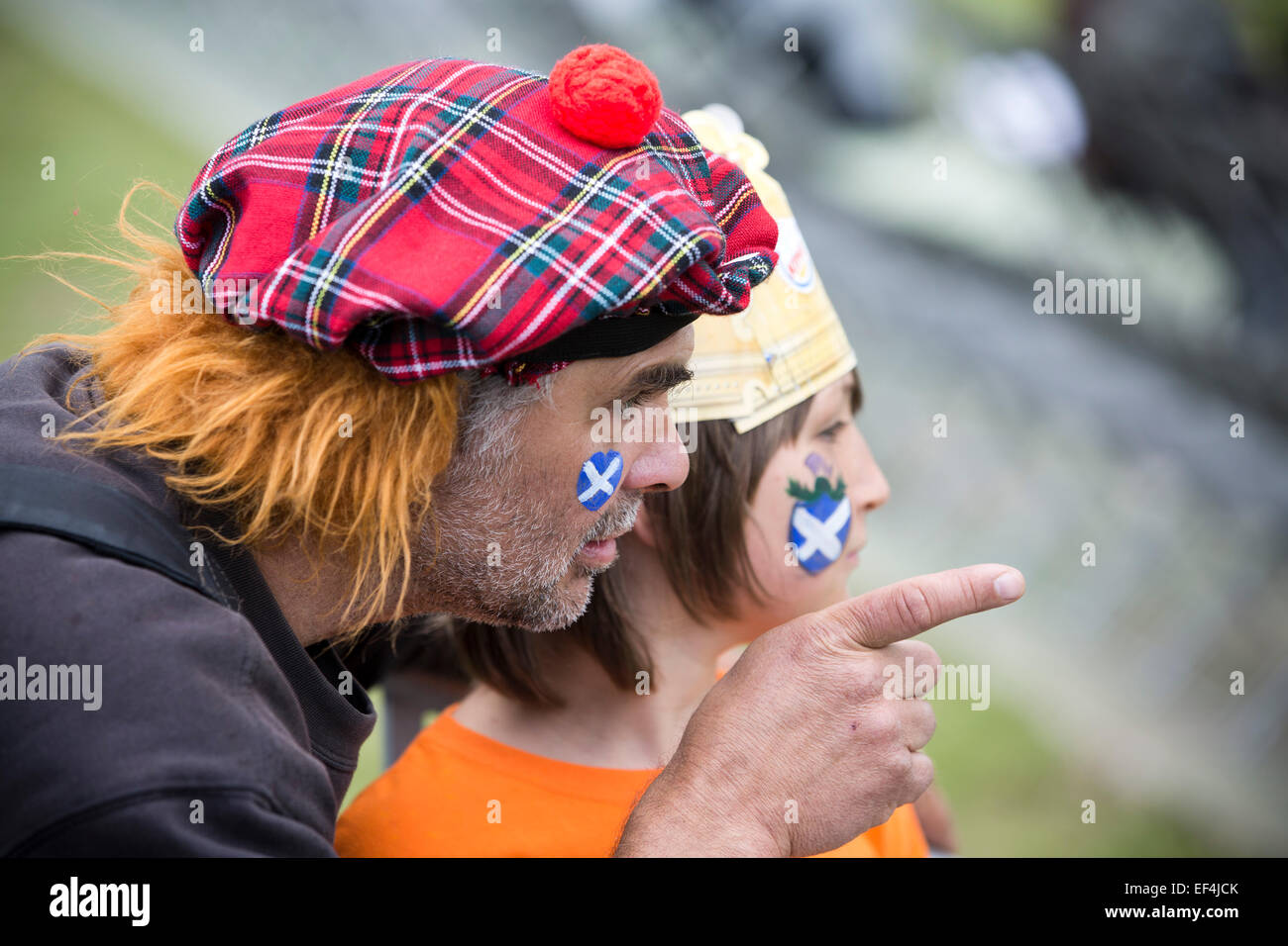 A man with a Scottish Jimmy Wig hat and his son watching the events at Bannockburn Live, at Bannockburn, Stirlingshire. - Stock Image