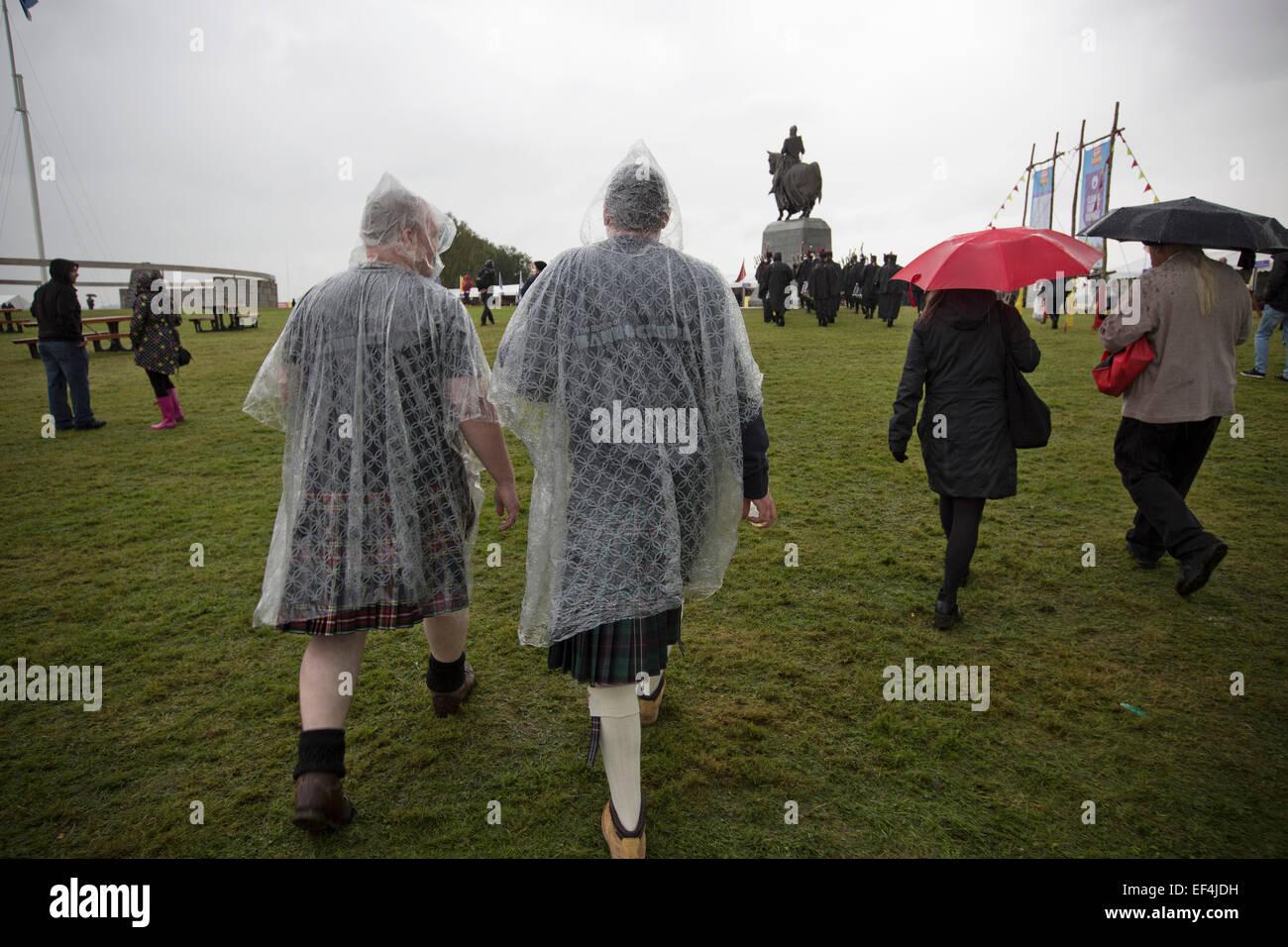 Two men dressed in kilts and rain ponchos during events at Bannockburn Live, at Bannockburn, Stirlingshire. - Stock Image