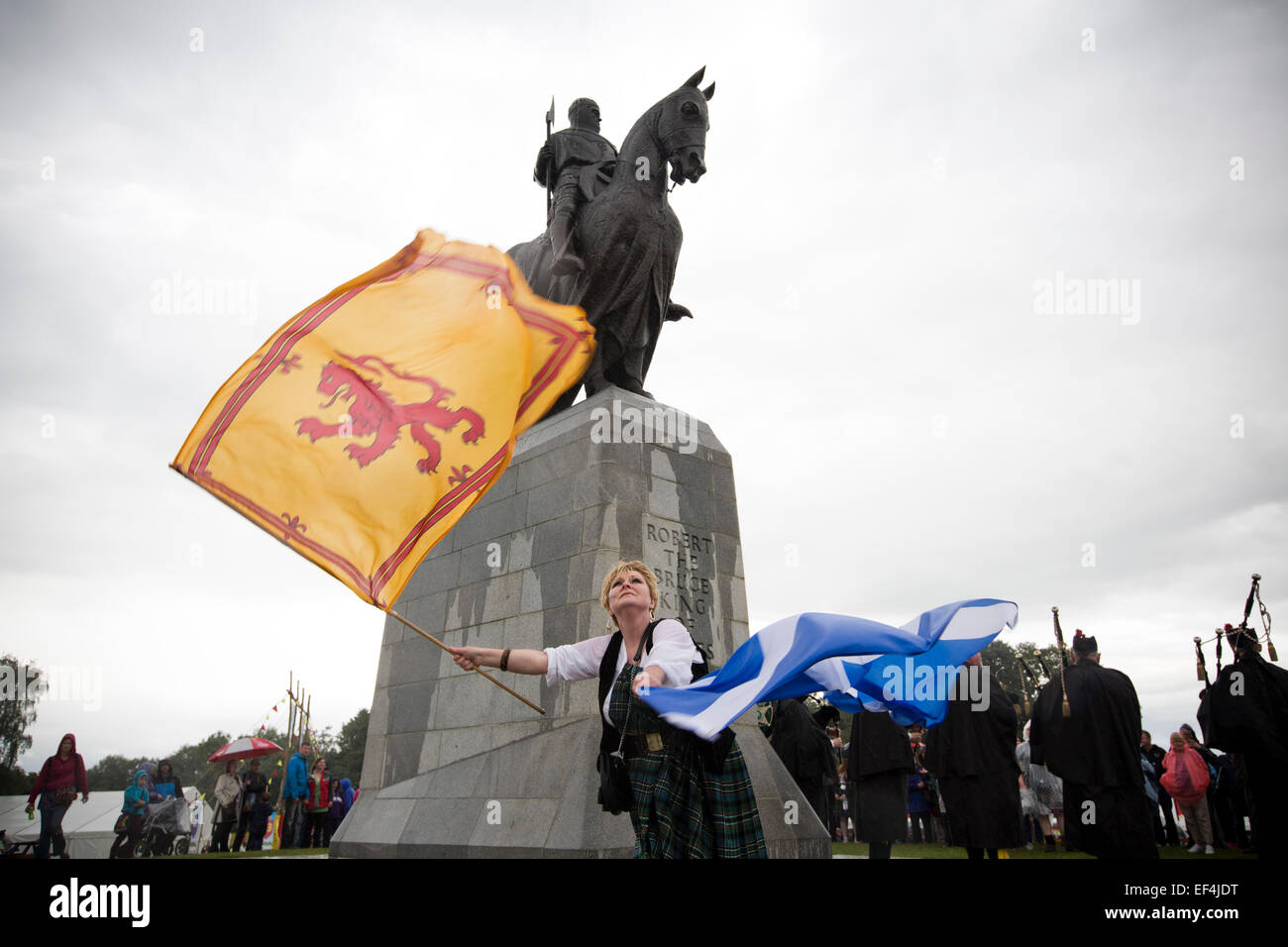 A woman with two Scottish flags dancing in front of the statue to Robert the Bruce during events at Bannockburn - Stock Image