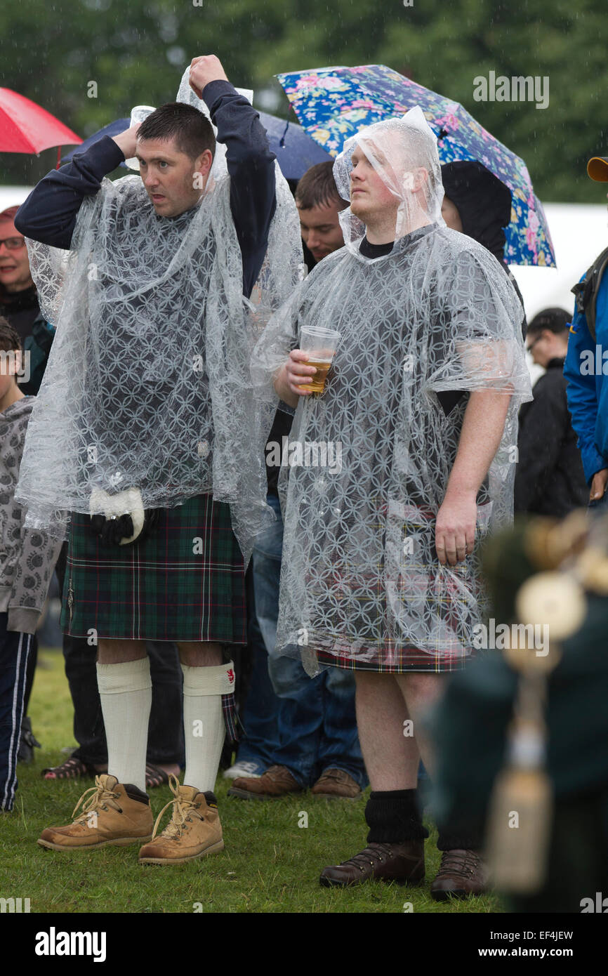 Two men dressed in kilts and rain ponchos during events at Bannockburn Live, at Bannockburn, Stirlingshire. Stock Photo