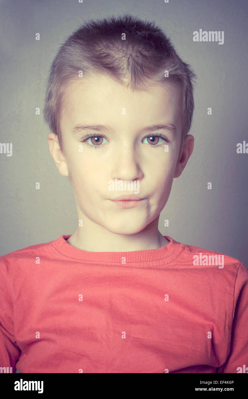 Young boy indoors looking at camera. - Stock Image