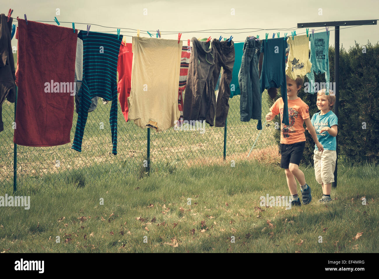 brothers playing outdoors laundry hanging - Stock Image