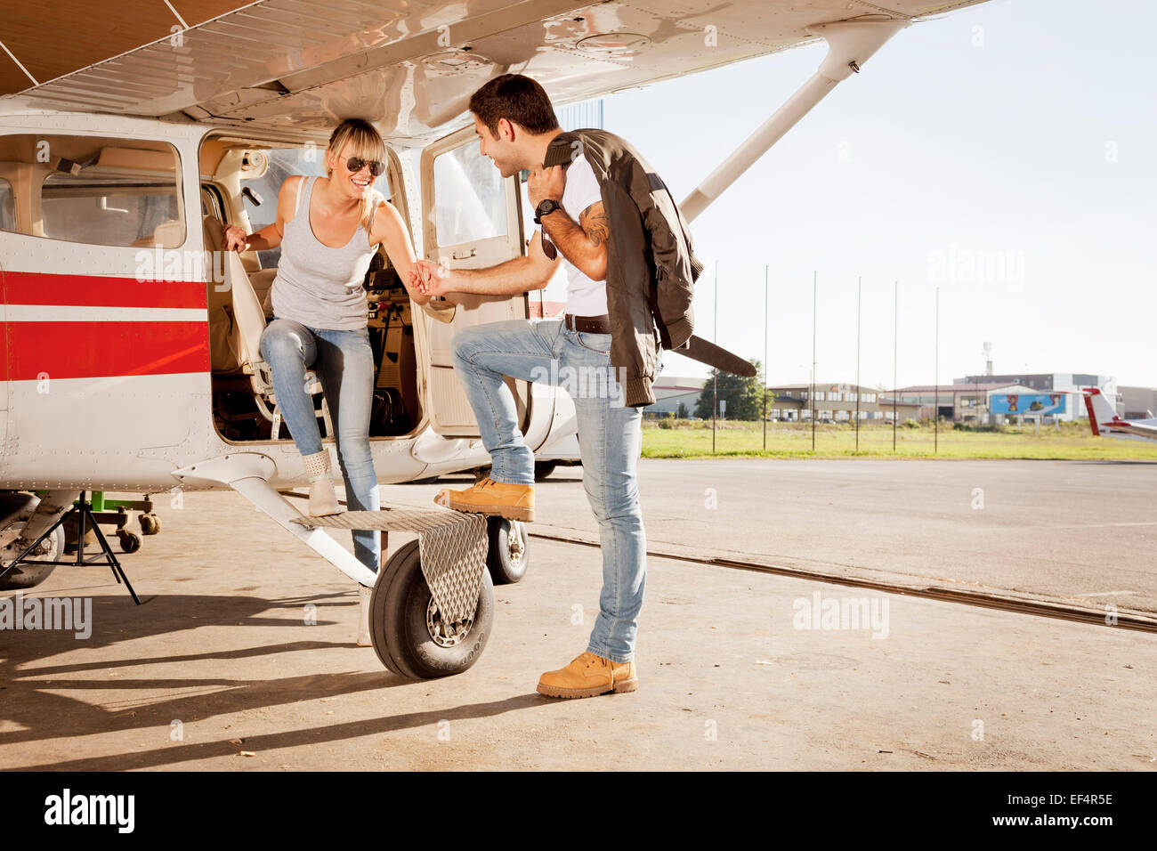 Young couple preparing  for start in private airplane - Stock Image