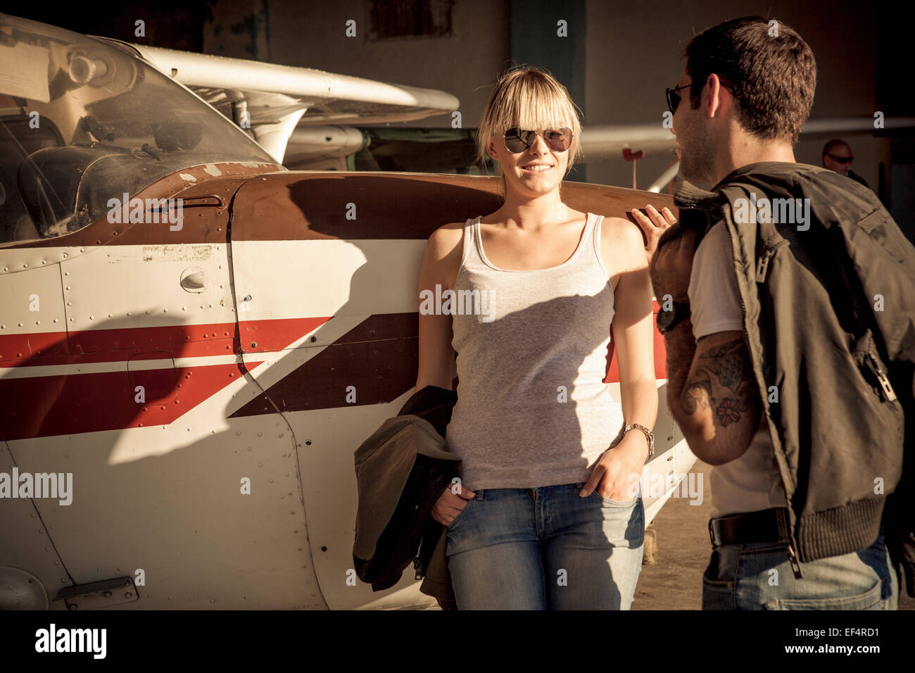 Young couple leaning against propeller airplane - Stock Image