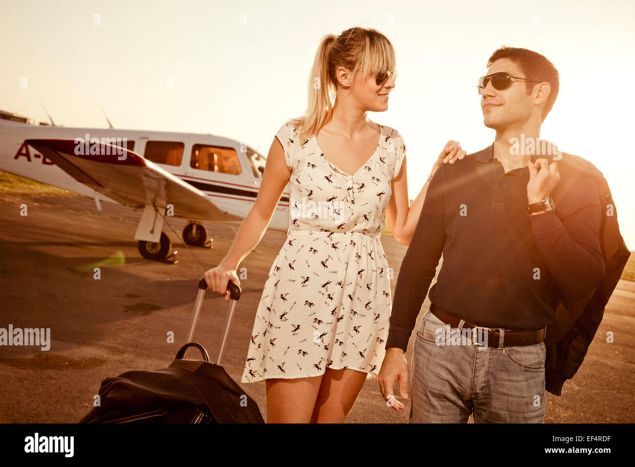 Couple with luggage in front of private airplane - Stock Image