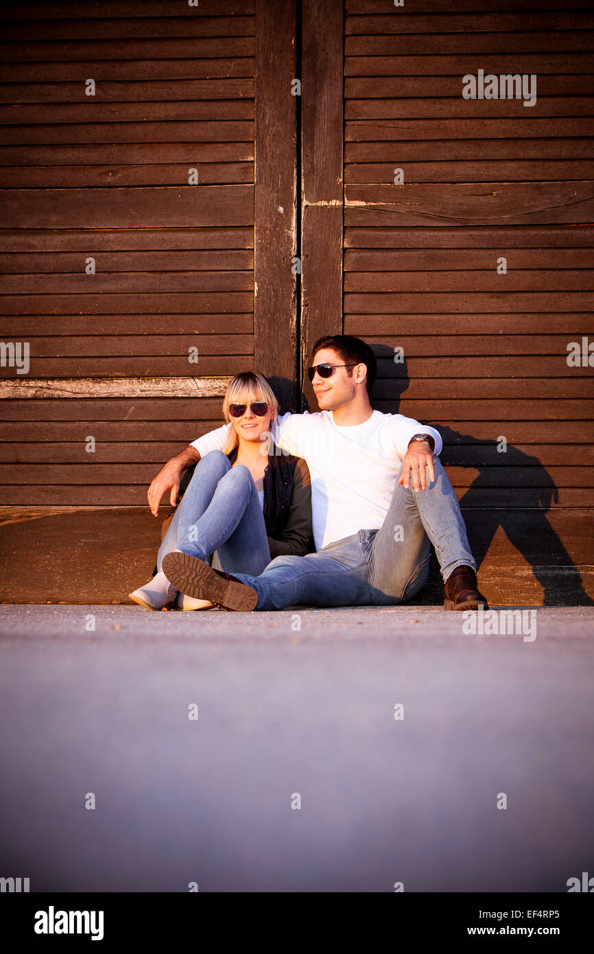 Young couple sitting side by side - Stock Image