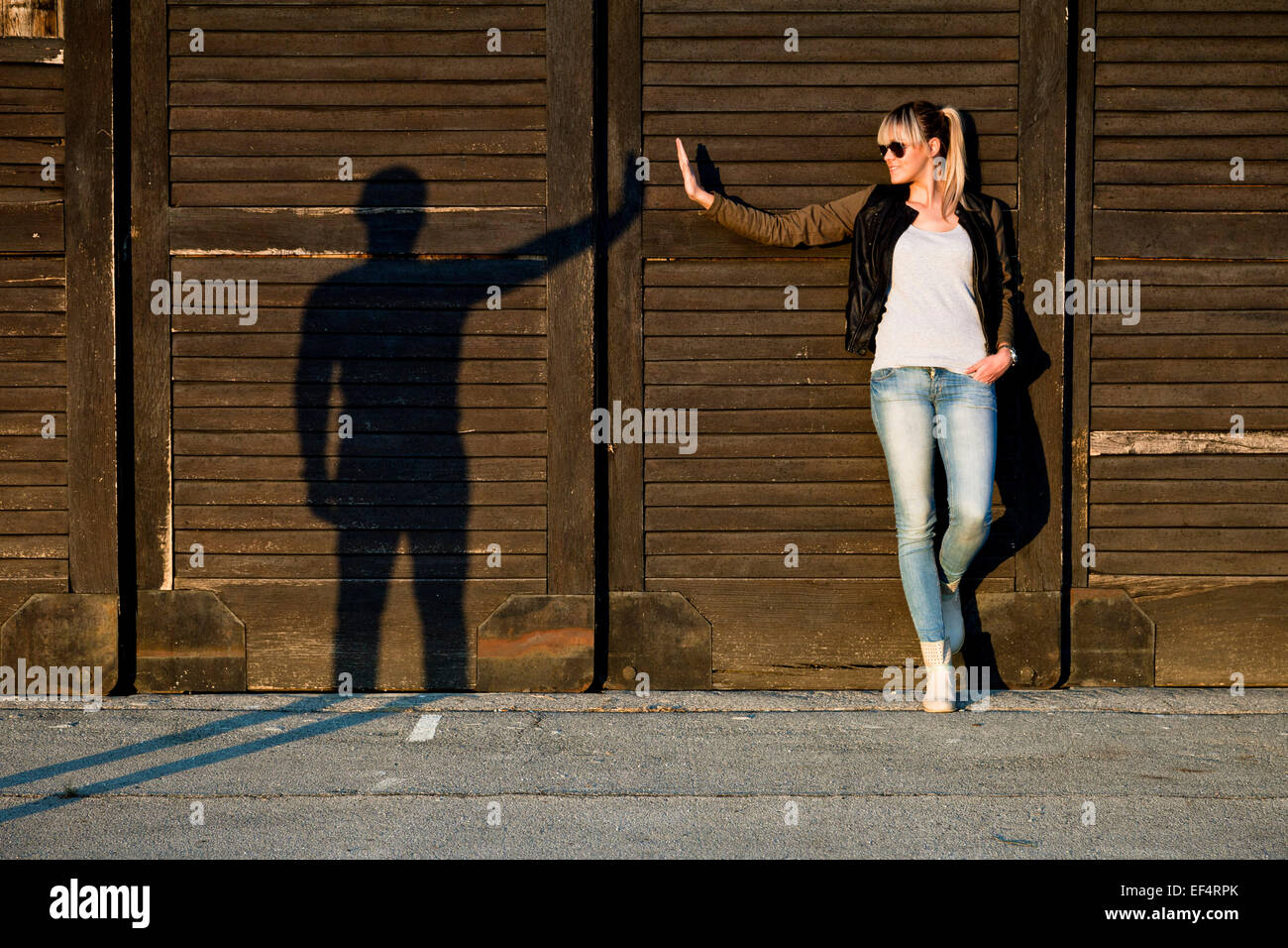 Young woman gesturing with silhouette of young man against wooden wall - Stock Image
