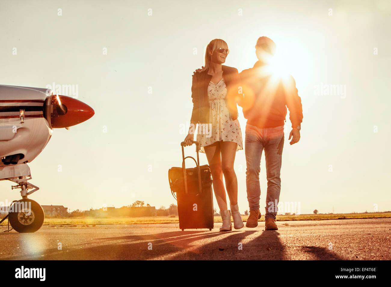 Young couple with luggage, propeller airplane in foreground - Stock Image