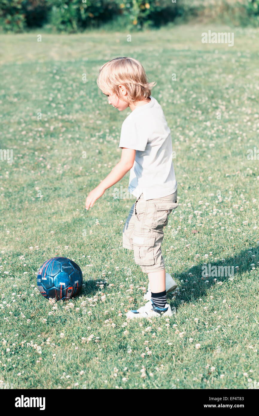 boy 6 years old playing ball garden - Stock Image