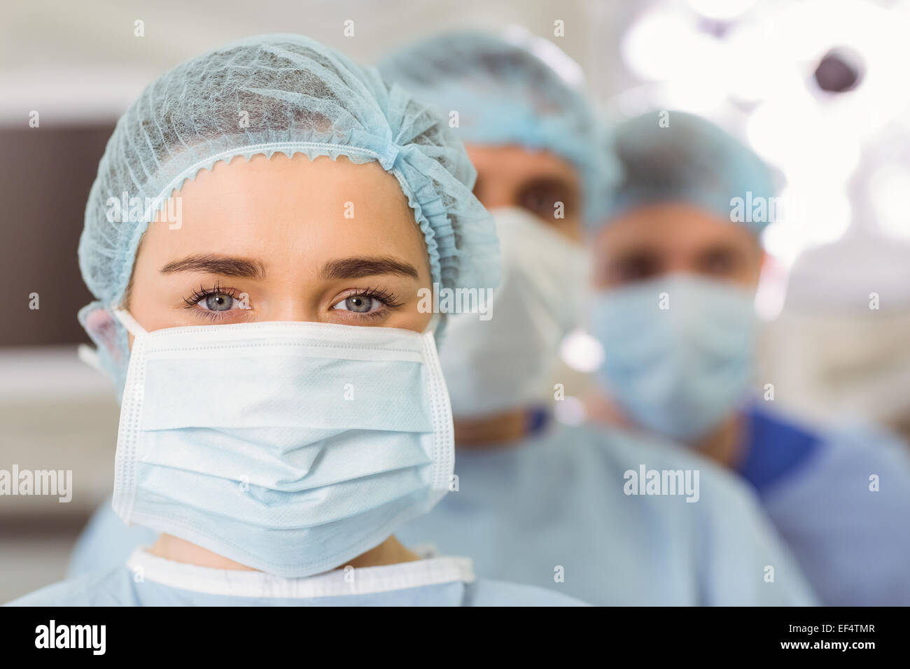Team of surgeons looking at camera - Stock Image