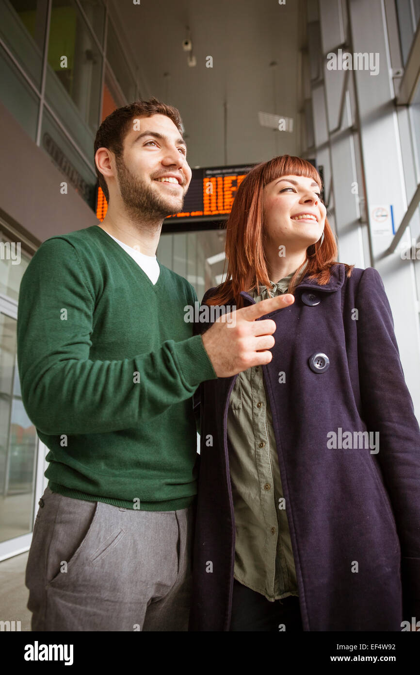 Young couple in airport building looking through window - Stock Image
