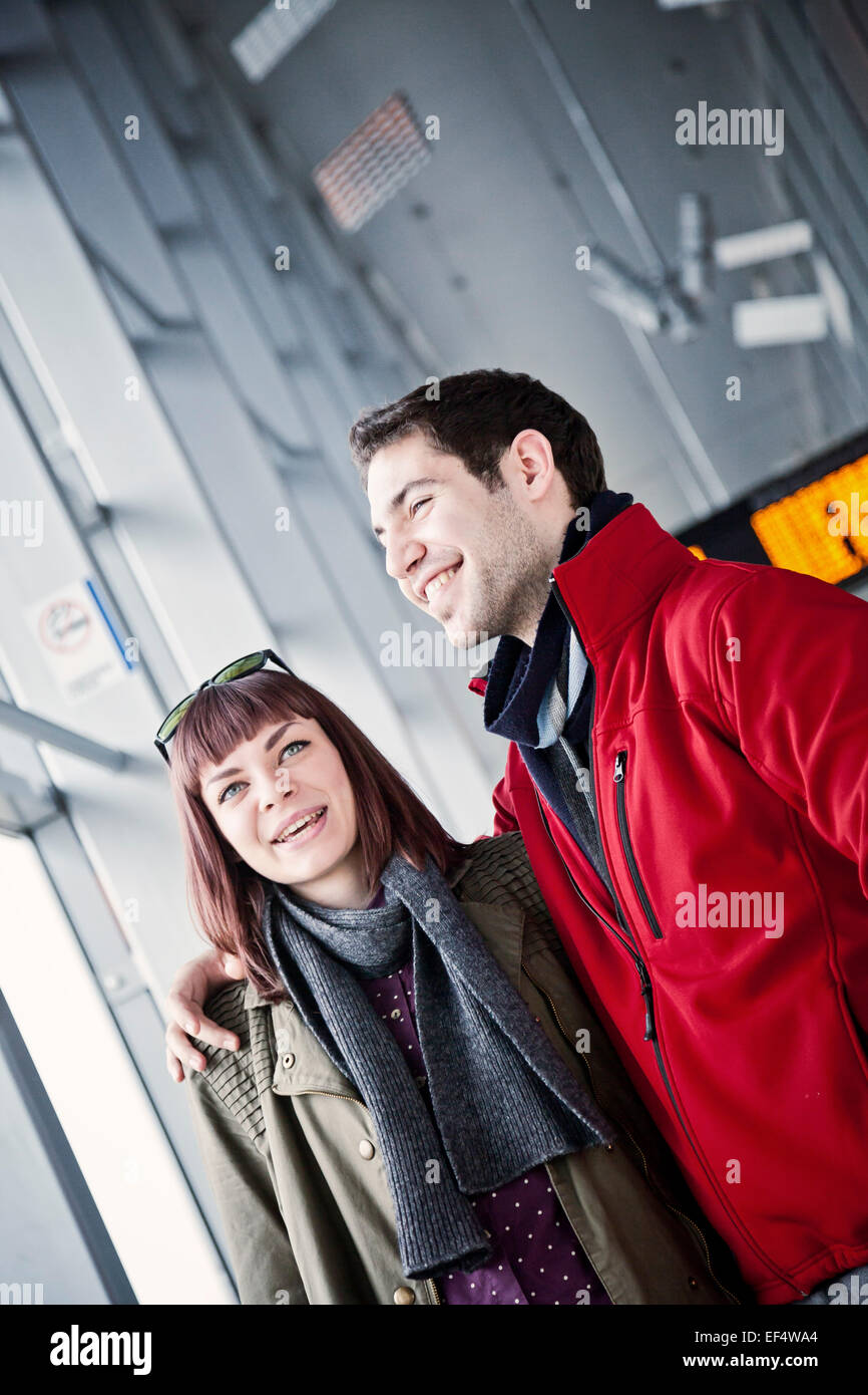 Happy young couple in airport building - Stock Image
