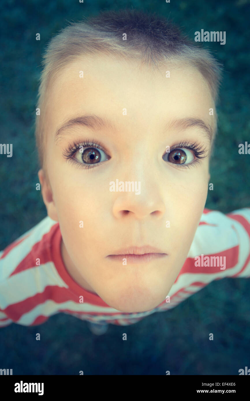 Young boy outdoors with wide eyes. - Stock Image