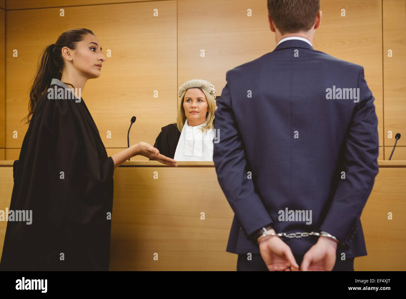 Lawyer talking with the criminal in handcuffs - Stock Image
