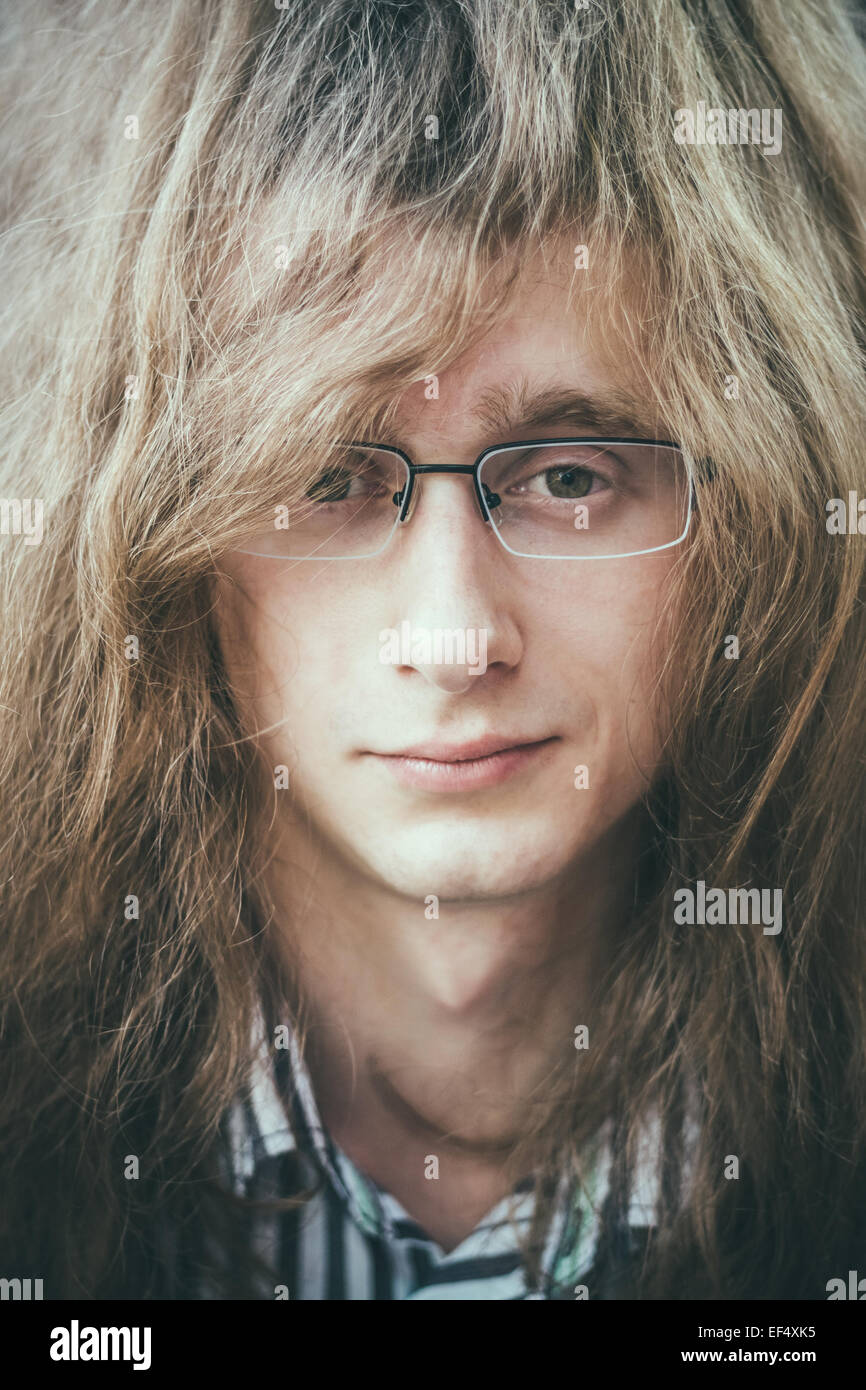 portrait of rock star young man guy with glasses and long hair stock