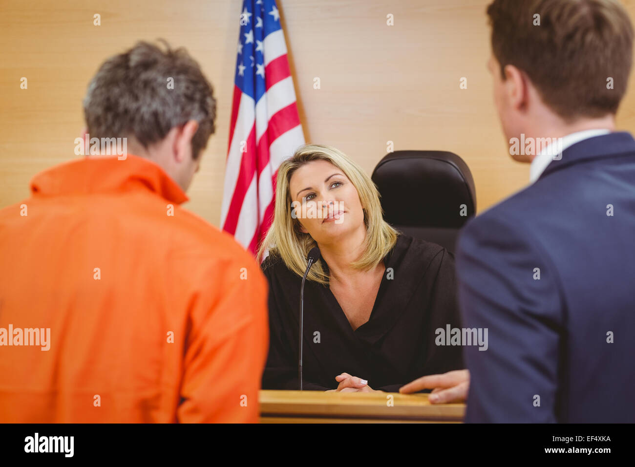 Lawyer speaking about the criminal in orange jumpsuit - Stock Image
