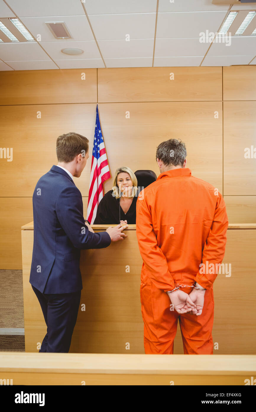 Lawyer and judge speaking next to the criminal in jumpsuit - Stock Image