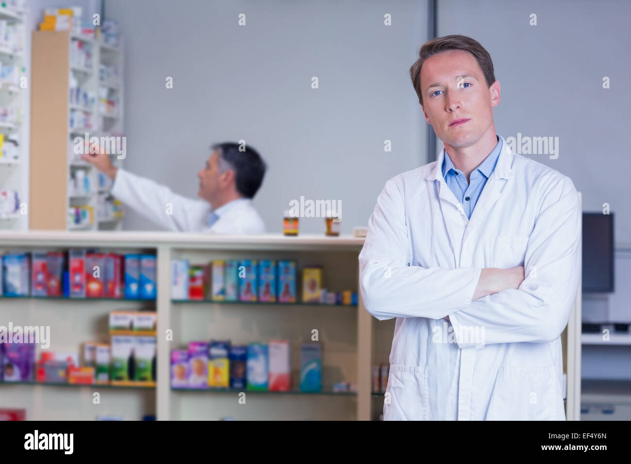 Unsmiling pharmacist standing with arms crossed - Stock Image